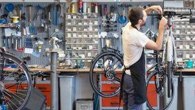 Le mécanicien amical et compétent de bicyclette dans un atelier répare un vélo images libres de droits