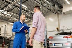 Le mécanicien automobile avec le presse-papiers et l'homme à la voiture font des emplettes Image libre de droits