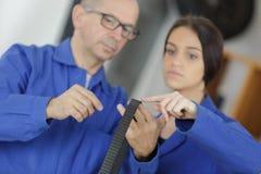 Le mécanicien automobile montre la voiture femelle d'entretien de stagiaire Images libres de droits