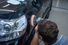 Le mécanicien automobile polit la voiture dans le service automatique photo libre de droits