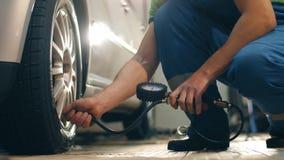 Le mécanicien automobile pompe la roue d'une voiture banque de vidéos