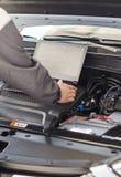 Le mécanicien avec l'ordinateur portable diagnostique la voiture images stock