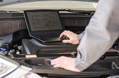 Le mécanicien avec l'ordinateur portable diagnostique la voiture image libre de droits