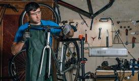 Le mécanicien compétent de bicyclette dans un atelier répare un vélo photo stock