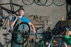 Le mécanicien compétent de bicyclette dans un atelier répare un vélo photos stock