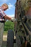 Le mécanicien d'équipement de ferme lubrifie le mecha de chaîne de rouleau d'huile à moteur photo stock
