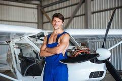 Le mécanicien d'aviation heureux se tenant avec des bras a croisé près du petit avion photos stock