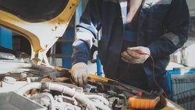 Le mécanicien dans l'atelier de voiture travaille avec des électricités de voiture - câblage électrique, voltmètre - petite entre Images stock