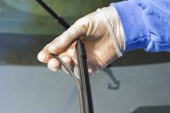 Le mécanicien dans les gants jetables tient la lame d'essuie-glace endommagée Image libre de droits