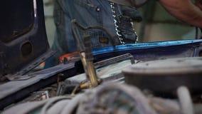 Le mécanicien de garçon vérifie la batterie de voiture banque de vidéos