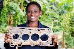 Le mécanicien de jeune femme tient une pièce endommagée de voiture Photos stock