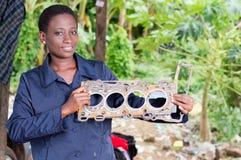 Le mécanicien de jeune femme tient une pièce endommagée de voiture Images libres de droits