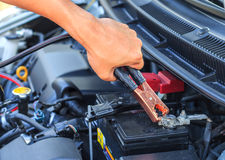 Le mécanicien de voiture emploie des câbles de pullover de batterie pour charger un batte mort Images stock