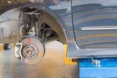 Le mécanicien de voiture remet inspecter un amortisseur dans l'étau au service des réparations Pièce de garage Photo stock