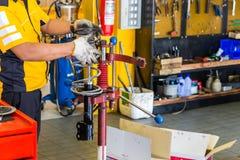Le mécanicien de voiture remet inspecter un amortisseur dans l'étau au service des réparations Pièce de garage Photographie stock libre de droits