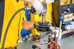 Le mécanicien de voiture remet inspecter un amortisseur dans l'étau au service des réparations Pièce de garage Photographie stock