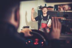 Le mécanicien de voiture souhaite la bienvenue au nouveau client à son service des réparations automatique photographie stock libre de droits