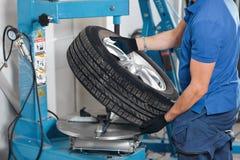 Le mécanicien enlève le plan rapproché de pneu de voiture Machine pour enlever le caoutchouc à partir du disque de roue photos libres de droits