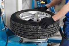 Le mécanicien enlève le plan rapproché de pneu de voiture Machine pour enlever le caoutchouc à partir du disque de roue Images stock