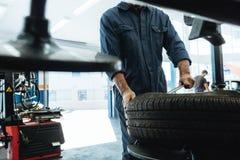 Le mécanicien enlève le pneu de voiture dans le garage photographie stock libre de droits