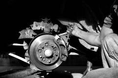 Le mécanicien est main tenant la clé réparant le circuit de freinage Photographie stock libre de droits