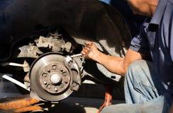 Le mécanicien est main tenant la clé réparant le circuit de freinage dans un gara Image stock