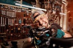 Le mécanicien fou scie le vélo par la scie circulaire Photo libre de droits