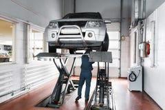 Le mécanicien inspectent le système de la suspension de la voiture soulevée images stock