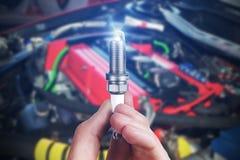 Le mécanicien juge une bougie d'allumage de pièce de rechange disponible Image stock