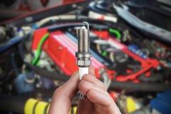 Le mécanicien juge une bougie d'allumage de pièce de rechange disponible Image libre de droits