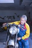 Le mécanicien masculin met en marche une motocyclette Photo libre de droits