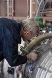 Le mécanicien plus âgé assemble le moteur d'aviation photographie stock