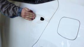 Le m?canicien rectifie la voiture avec le papier sabl? avant la peinture ? la station service banque de vidéos
