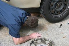 Le mécanicien regarde sous le véhicule Photo libre de droits