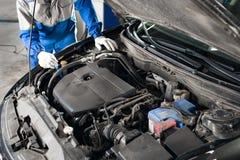 Le mécanicien remet la vérification de l'utilité de la voiture dans le capot ouvert, fin  photographie stock libre de droits