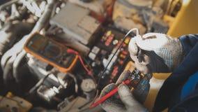 Le mécanicien travaille avec des électricités de voiture - câblage électrique, voltmètre Photographie stock libre de droits