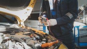 Le mécanicien travaille avec le voltmètre - électricités de voiture - câblage électrique Photo libre de droits