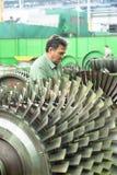 Le mécanicien travaille avec une partie de moteur d'aviation Photographie stock libre de droits