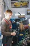 Le mécanicien travaille avec le voltmètre - électricités de voiture - câblage électrique photo stock