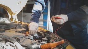 Le mécanicien travaille des électricités de voiture avec le voltmètre - câblage électrique Photographie stock