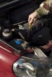 Le mécanicien vérifie le jaugeur de niveau d'huile à moteur Image stock