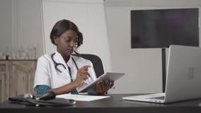 Le médecin africain attirant parlant sur le travail de téléphone avec l'ordinateur portable, dans l'hôpital de coffret, écrivent  banque de vidéos