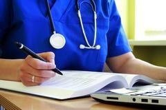 Le médecin avec le stéthoscope écrit image stock