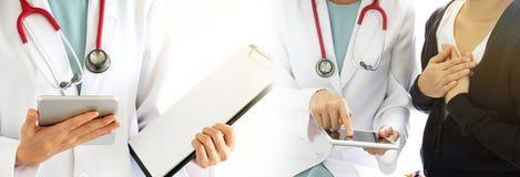 Le médecin discute avec le patient au sujet des résultats d'examen de santé à l'aide de la tablette photos stock