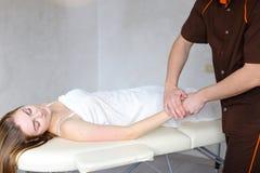 Le médecin expérimenté de type applique manuellement la méthode manuelle de massage Photos libres de droits