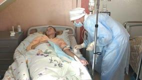 Le médecin généraliste habile met le compte-gouttes dans l'hôpital L'anesthésiste de docteur de jeune femme met le compte-gouttes photos libres de droits