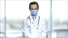 Le médecin masculin mûr met sur le masque protecteur banque de vidéos