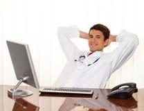 Le médecin réussi s'assied à un bureau photos libres de droits