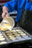 Le mélange de versement de Brule de crème de chef au-dessus de l'étain moule Photographie stock