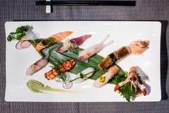 Le mélange du nigiri différent sur une feuille en bambou a servi avec le daikon et Images libres de droits